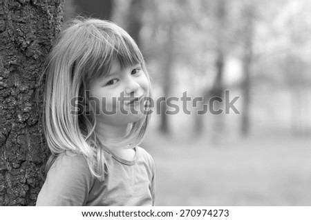 Portrait of smiling little girl in spring forest.