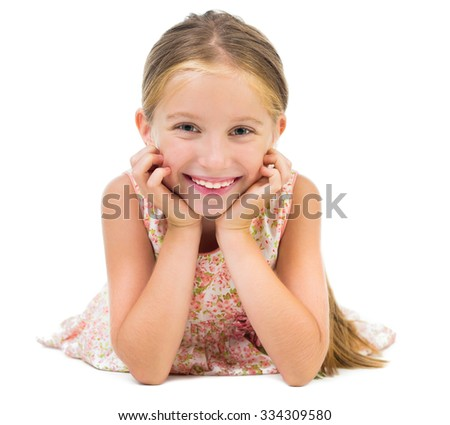portrait of smiling little girl lying on the floor isolated on white background - stock photo
