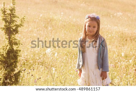 Portrait of smiling little girl on meadow, summer day in nature.