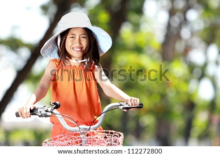 portrait of smiling little girl riding bicycle outdoor
