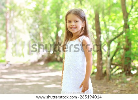 Portrait of smiling little girl walking in the forest, sunny summer day - stock photo