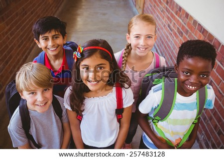 Portrait of smiling little school kids in school corridor - stock photo