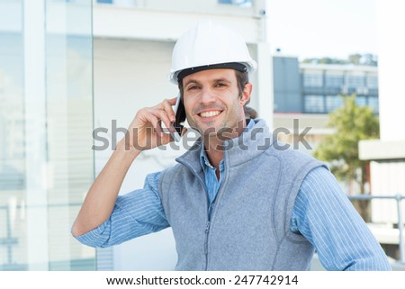 Portrait of smiling male architect using mobile phone outdoors - stock photo