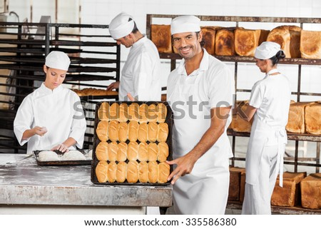 Portrait of smiling male baker showing baked breads while coworkers working in bakery - stock photo