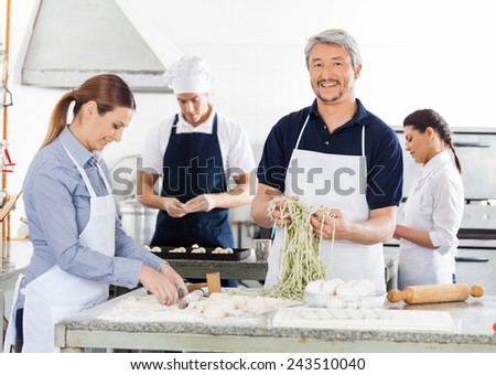 Portrait of smiling male chef with colleagues preparing pasta in commercial kitchen - stock photo