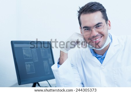 Portrait of smiling male dentist with computer monitor