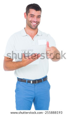Portrait of smiling male handyman with clipboard gesturing thumbs up on white background