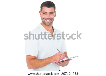 Portrait of smiling male handyman writing on clipboard over white background