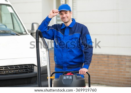 Portrait of smiling male janitor with vacuum cleaner wearing cap while standing on street - stock photo