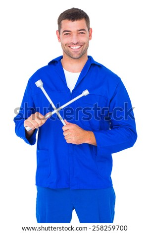 Portrait of smiling male mechanic holding lug wrench on white background