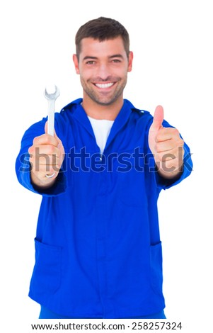 Portrait of smiling male mechanic holding spanner while gesturing thumbs up on white background - stock photo