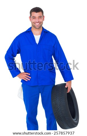 Portrait of smiling male mechanic holding tire on white background