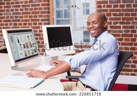 Portrait of smiling male photo editor using computer in the office - stock photo