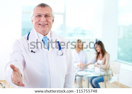 Portrait of smiling male practitioner looking at camera in hospital - stock photo