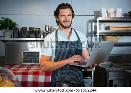 Portrait of smiling male staff using laptop at counter in coffee shop