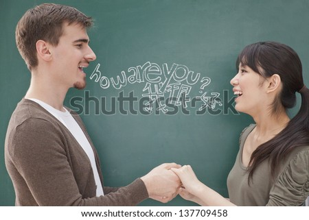 Portrait of smiling male teacher and student in front of chalkboard holding hands - stock photo