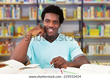 Portrait of smiling male university student studying at table in library