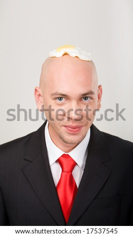 Portrait of smiling male with omelet on top of bald head - stock photo
