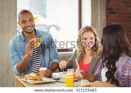 Portrait of smiling man having burger with colleagues in office