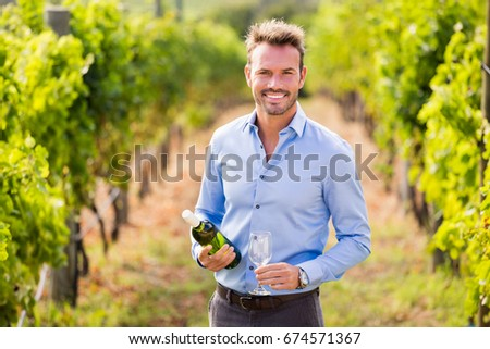 Portrait of smiling man holding wine bottle and glass at vineyard on sunny day