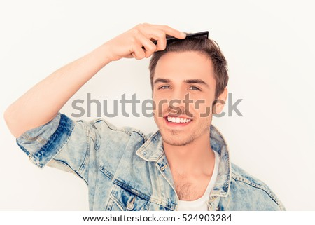 Portrait of smiling  man in jeans jacket combing his hair.