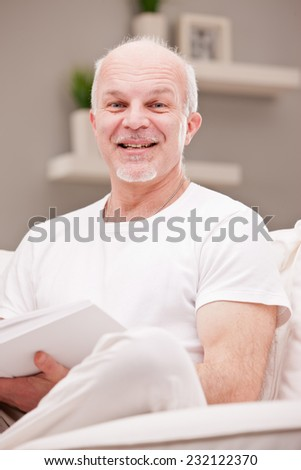 portrait of smiling man on a couch in a white living room reading a book