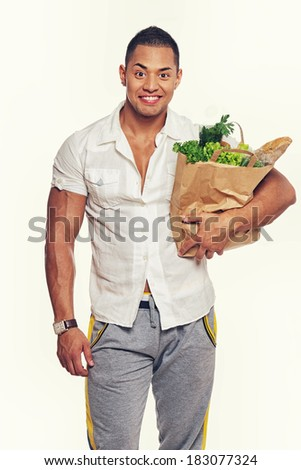 Portrait of smiling man posing in studio with food - stock photo