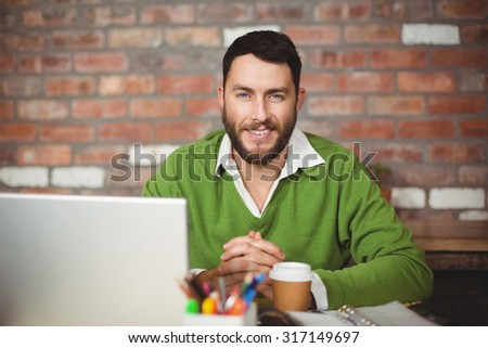 Portrait of smiling man sitting in creative office