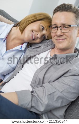 Portrait of smiling man sitting with woman at home - stock photo