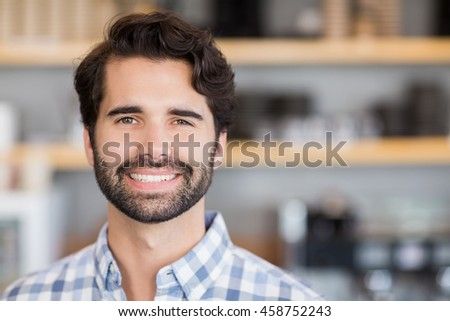 Portrait of smiling man standing at cafe
