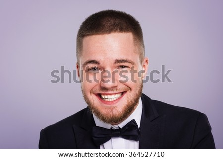 Portrait of smiling man wearing a tuxedo with bow-tie on lilac background.  - stock photo