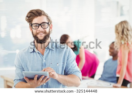 Portrait of smiling man wearing eyeglasses using digital tablet while standing at office - stock photo