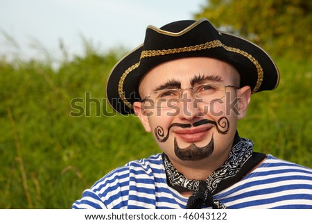 portrait of smiling man with drawed beard and whiskers in pirate suit in early fall evening park - stock photo