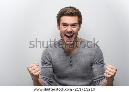 Portrait Of Smiling Man With Fists Up. happy guy standing against white background - stock photo