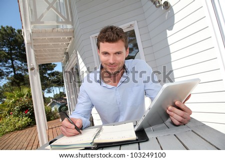 Portrait of smiling man working at home on tablet - stock photo