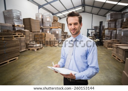 Portrait of smiling manager holding clipboard in warehouse