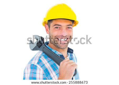 Portrait of smiling manual worker holding adjustable spanner on white background
