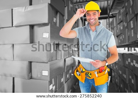 Portrait of smiling manual worker holding clipboard against shelves with boxes in warehouse