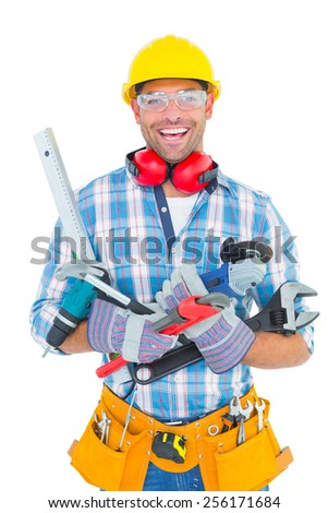 Portrait of smiling manual worker holding various tools on white background - stock photo
