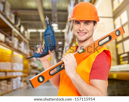 Portrait of smiling manual worker with tools at warehouse