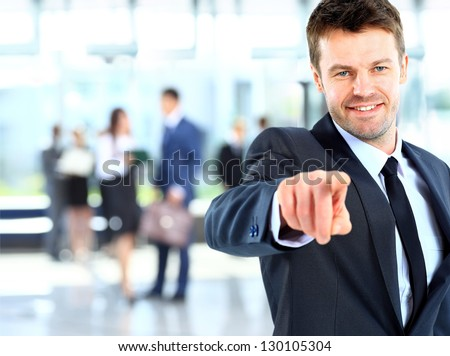 Portrait of smiling mature business man pointing at you in office - stock photo