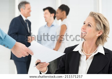 Portrait Of Smiling Mature Businessman Giving Document To Colleague