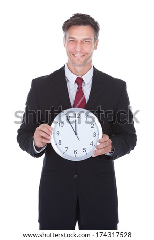 Portrait Of Smiling Mature Businessman Holding Clock - stock photo