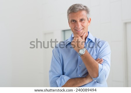 Portrait Of Smiling Mature Businessman With Hand On Chin In His Office - stock photo