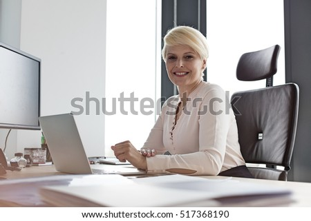 Portrait of smiling mature businesswoman sitting at desk in office