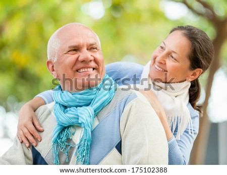 Portrait of smiling mature couple in sweaters at autumn park