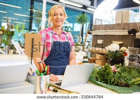 Portrait of smiling mature female florist using laptop at counter in flower shop - stock photo