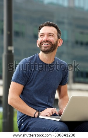 Portrait of smiling mature man sitting outdoors with laptop and looking away