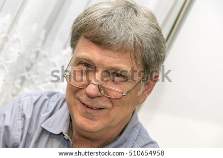 portrait of smiling mature man with reading glasses