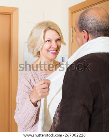 Portrait of smiling mature spouses saying goodbye at doorway - stock photo